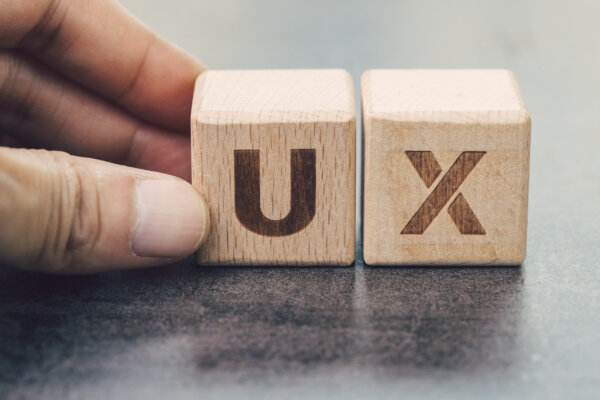 UX development, User Experience design concept, hand building cube wooden block with alphabet U and X on blackboard, user centric in modern world business, product and service design